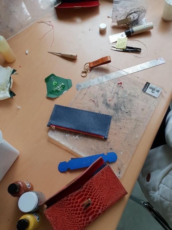 테이블에 놓여있는 가죽공예 작품과 재료 사진